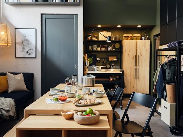 Ein RÅVAROR Esstisch, ein RÅVAROR Regal mit Rollen und RÅVAROR Klappstühle stehen in der Mitte eines Apartments. Auf dem Tisch stehen Teller, Schüsseln und Gläser.