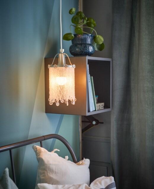 Ein Regal und SÖDER Hängeleuchte neben einem Bett