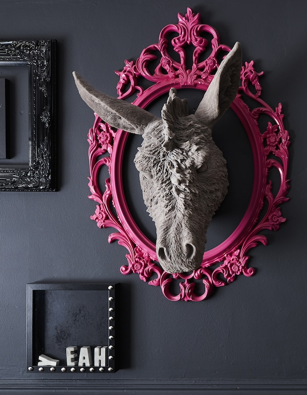 Ein rosafarben gestalteter UNG DRILL Rahmen oval/weiß an einer schwarzen Wand.
