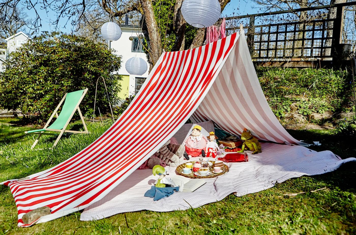 Ein rot-weiß gestreiftes Stofftuch wird zum Zelt für Kinder im Garten mit Kuscheltieren.