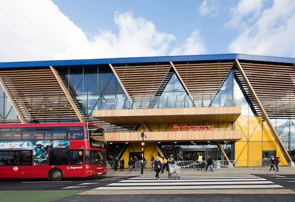 Ein roter Bus fährt an der Fassade aus Holz und Glas am IKEA Einrichtungshaus in London Greenwich vorbei.