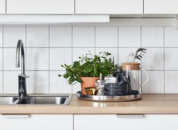 Ein rundes Tablett, auf dem eingetopfte Kräuter zu sehen sind. Auf der Arbeitsfläche stehen Küchenutensilien und eine Karaffe. U. a. mit SINNERLIG Hängeleuchte in Bambus.