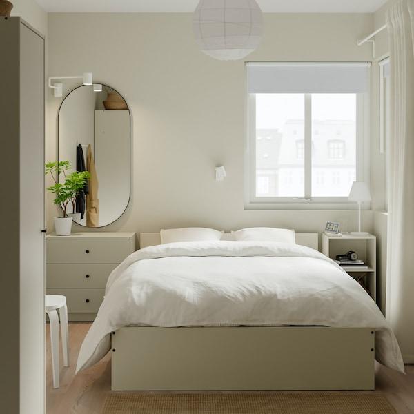 Ein sauberes und aufgeräumtes Schlafzimmer mit beigen Möbeln und weißem Bettzeug, einem Spiegel an der Wand und einem Kleiderschrank an der Seite.