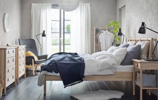Ein Schlafzimmer in Neutraltönen mit einem Bettgestell aus Holz, einer Kommode und einem Ablagetisch