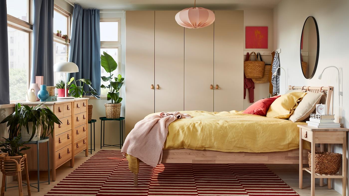 Ein Schlafzimmer mit einem BJÖRKSNÄS Bettgestell, Kommoden und Ablagetisch. An der Rückwand ist ein PAX Kleiderschrank zu sehen, hinzu kommen mehrere Tabletttische.