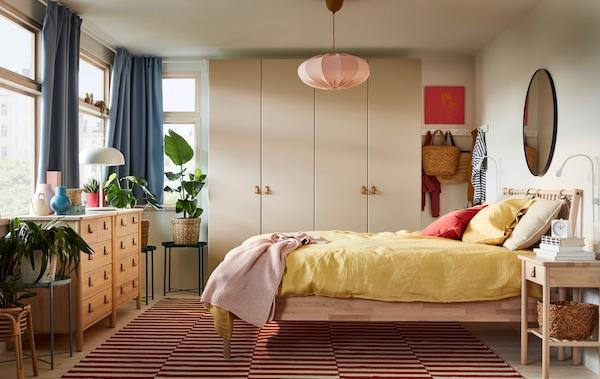 Ein Schlafzimmer mit einem BJÖRKSNÄS Bettgestell und zwei Kommoden aus Birkenholz, einem graubeigen Kleiderschrank, blauen Gardinen und gelben Betttextilien.