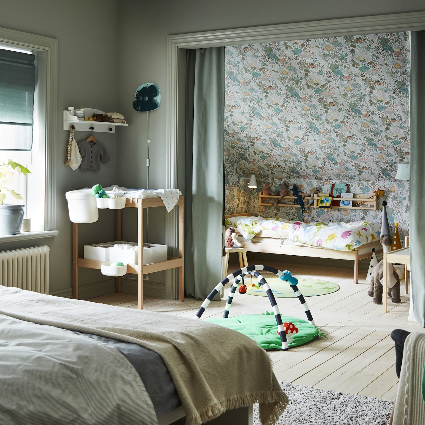 Ein Schlafzimmer mit einem Doppelbett, einem Wickeltisch und Babyaccessoires. Ein SNIGLAR Juniorbettgestell steht in einer Nische hinter einem grünen Vorhang.