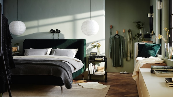 Ein Schlafzimmer mit einem grünen TUFJORD Bettgestell und zwei SKURUP Leuchten an der Wand dahinter. Einige NORDLI Schubladenelemente sind an der seitlichen Wand positioniert.