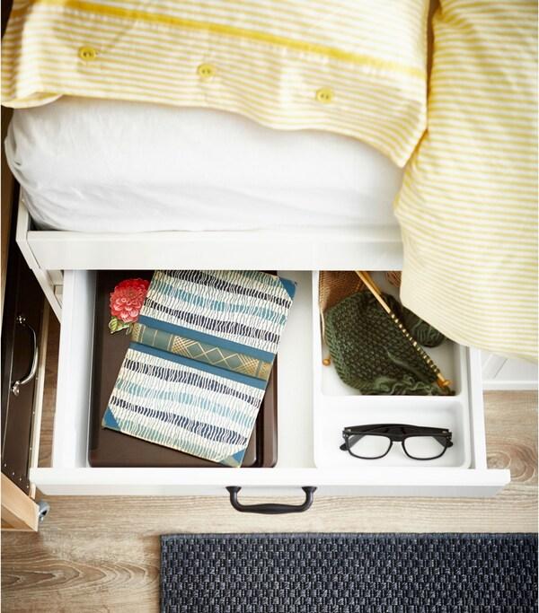 Ein Schlafzimmer mit einem selbst gestalteten Bettpodest aus METOD Küchenschränken, u. a. mit FINTORP Stangen in Schwarz. Eine niedrige MAXIMERA Schublade in Weiß neben dem Bett ist geöffnet und zeigt ein Buch und eine Brille.