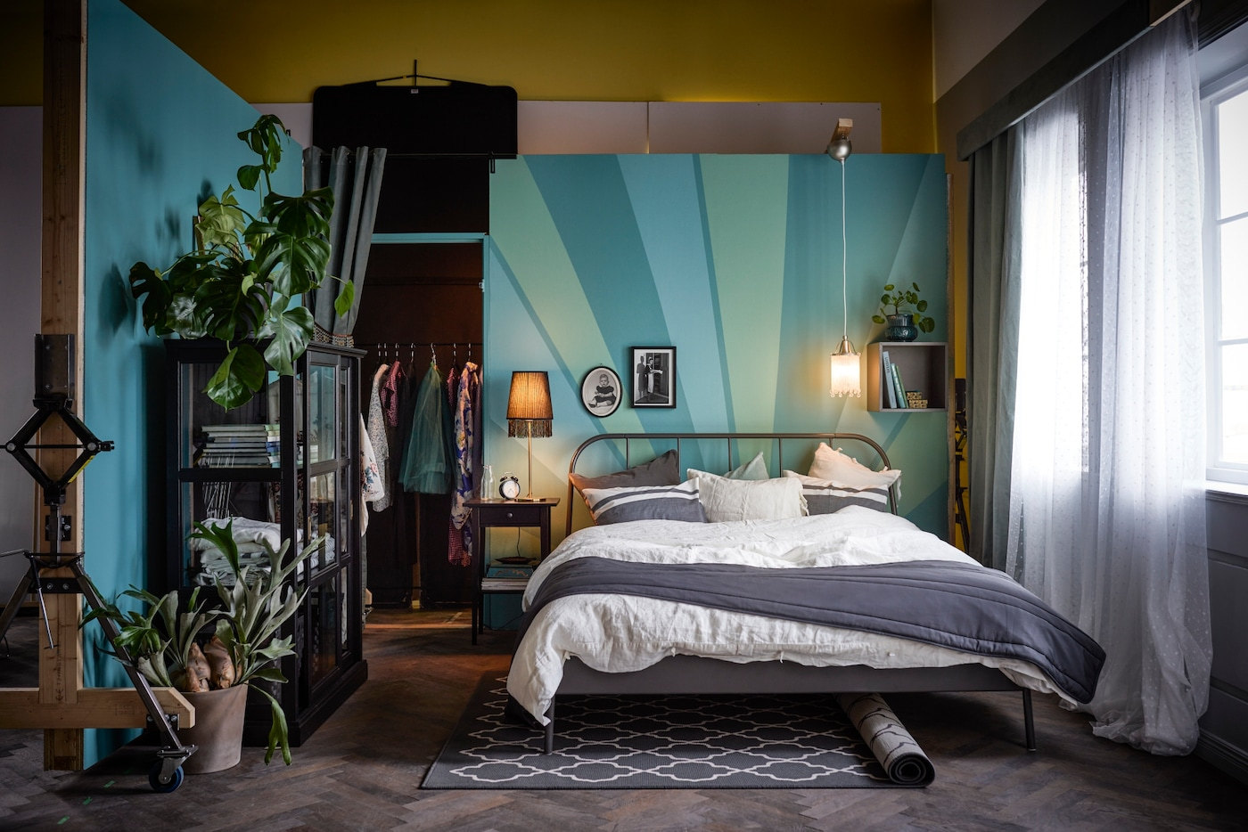 Ein Schlafzimmer mit grau-weißen Accessoires, Textilien & Möbeln, aber türkis-grünen Wänden