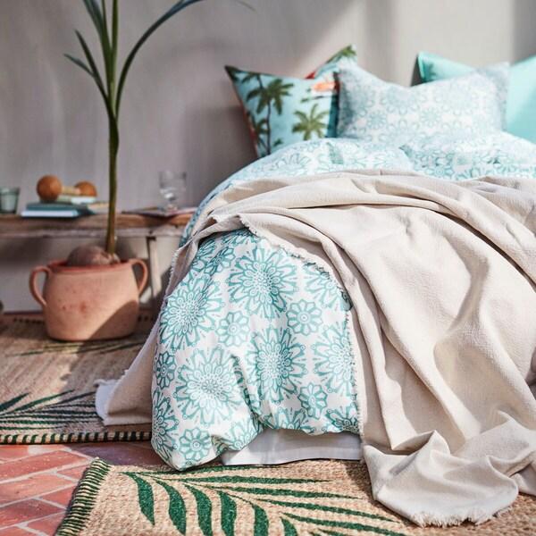 Ein Schlafzimmer mit türkis gemusterter Bettwäsch und grünen Kissen vor einer dunkelgrünen Wand.