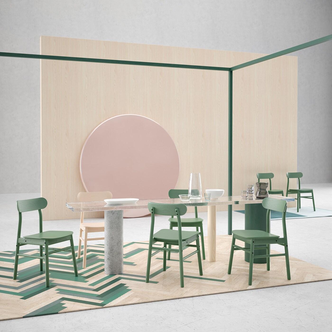 Ein schlichter Raum mit einem Steintisch mit grünen & beigen Stühlen auf einem grün-beigen Boden.