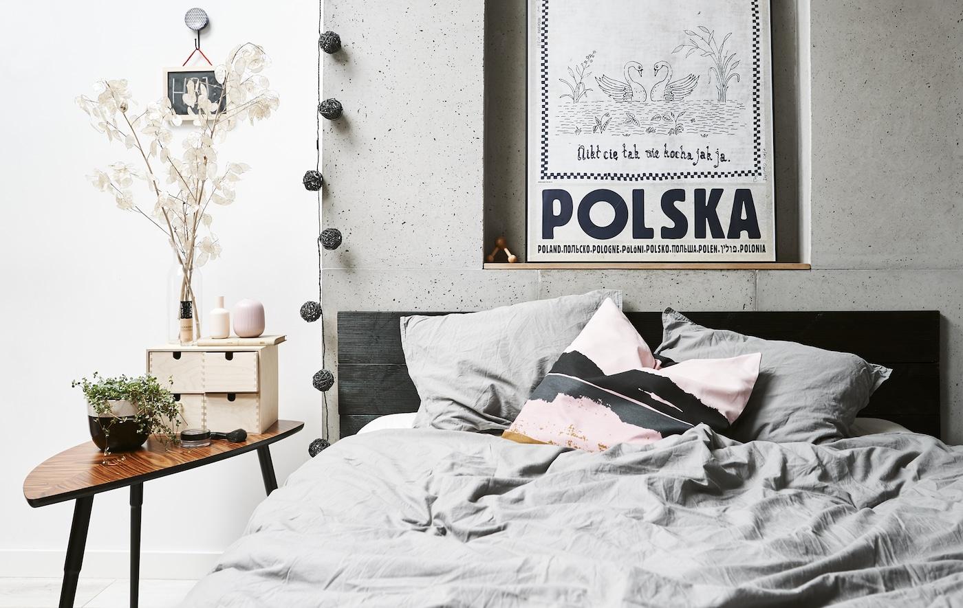 Ein schlichtes, in Grau-Weiß gehaltenes Schlafzimmer mit Doppelbett & braunem Ablagetisch