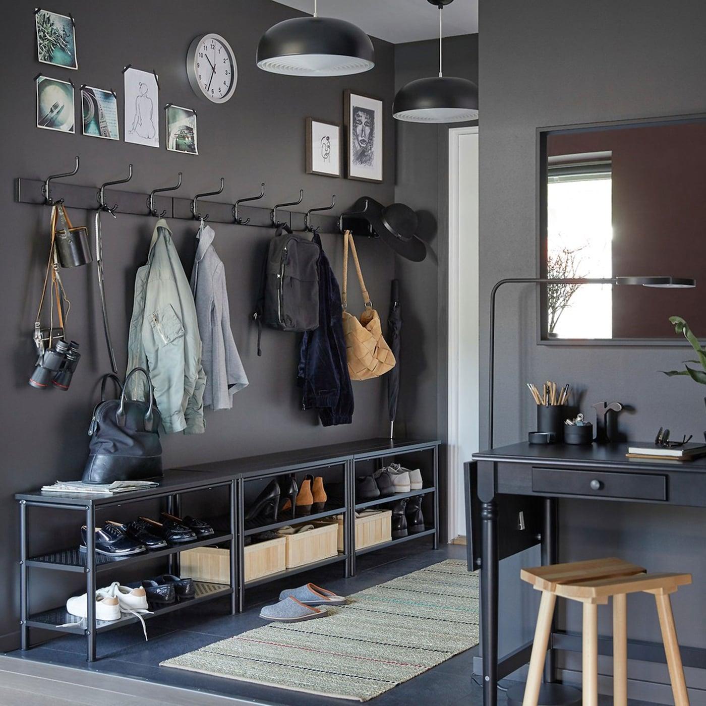 Ein schmaler Flur mit drei PINNIG Bänken mit Schuhablage in Schwarz, drei PINNIG Haltern mit 3 Haken in Schwarz und INGATORP Schreibtisch in Schwarz