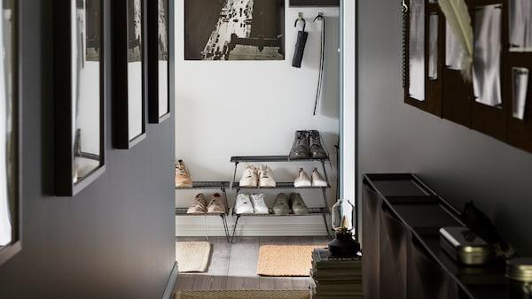 Ein schmaler Flur mit Fotos an den Wänden, u. a. mit mehreren übereinander gestapelten GREJIG Schuhaufbewahrungen und ein paar SVENSÅS Notiztafeln.