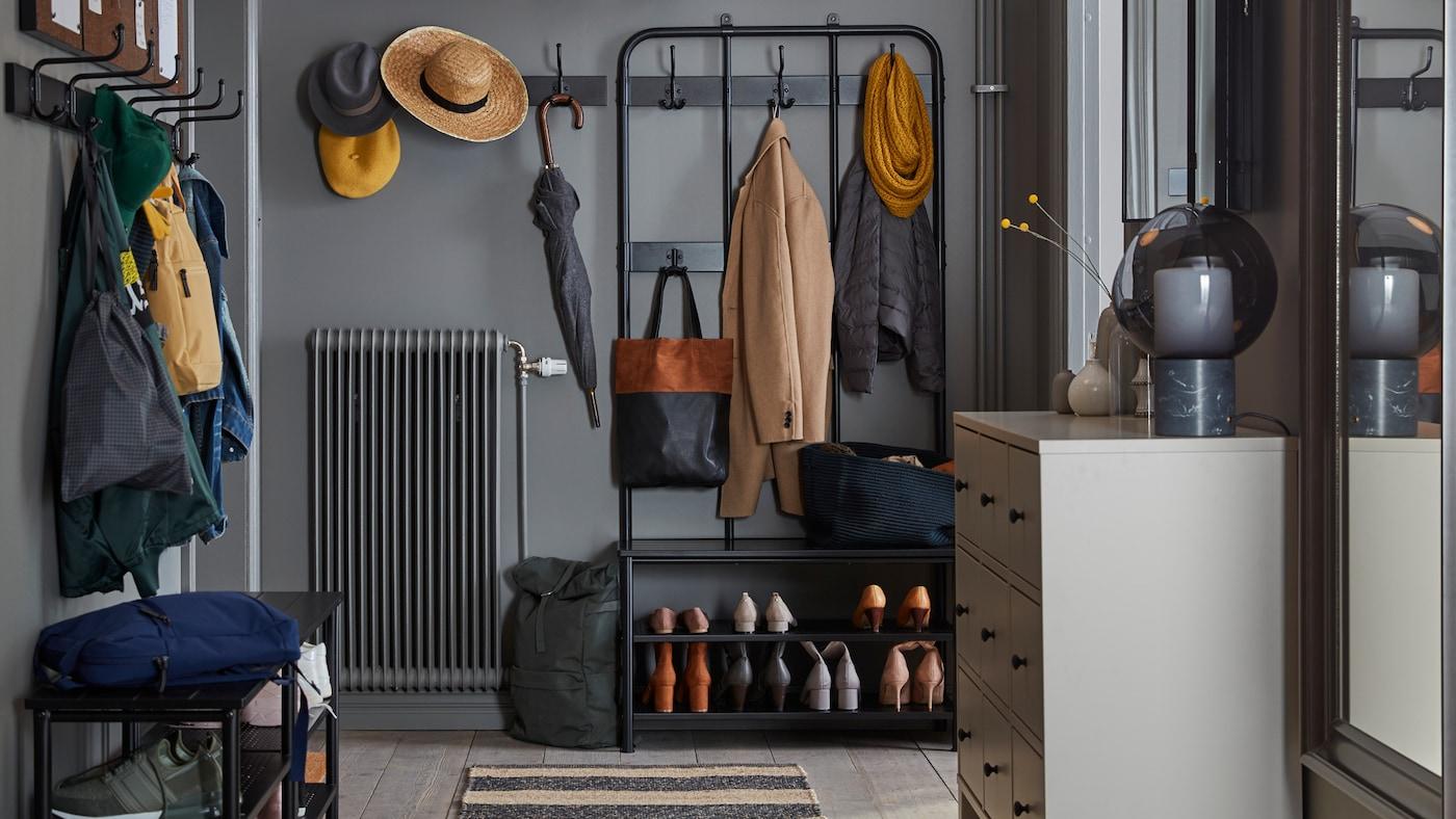 Ein schmaler, in Grautönen gehaltener Flur, u. a. mit einem PINNIG Garderobenständer mit Bank, auf der Seite mit Hakenleisten für Jacken, Mützen, Hüte und Taschen. Unter der Bank sind Schuhe zu sehen.