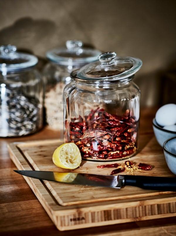 Ein Schneidebrett aus Holz, auf dem ein Messer und eine Zitronenhälfte zu sehen sind. Dahinter steht ein Glas mit roten Chilis.