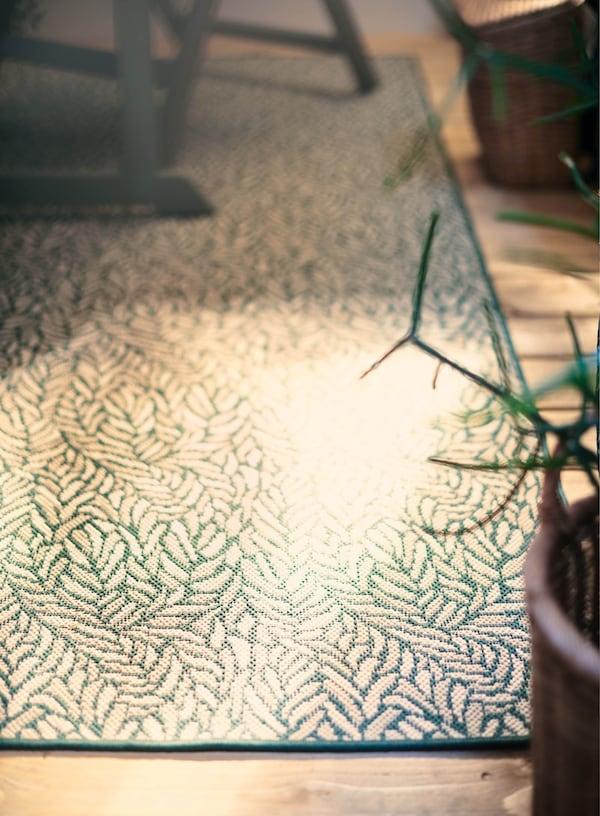 Ein schön gemusterter SKELUND Teppich für den Außenbereich, der von der Sonne angeschienen wird.