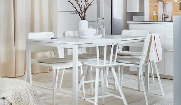 Ein schönes und helles Esszimmer mit weißen Möbeln.