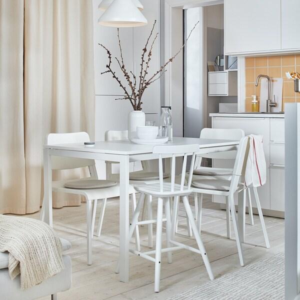 Ein schönes und helles Esszimmer mit weißen Möbeln, das günstig eingerichtet wurde.