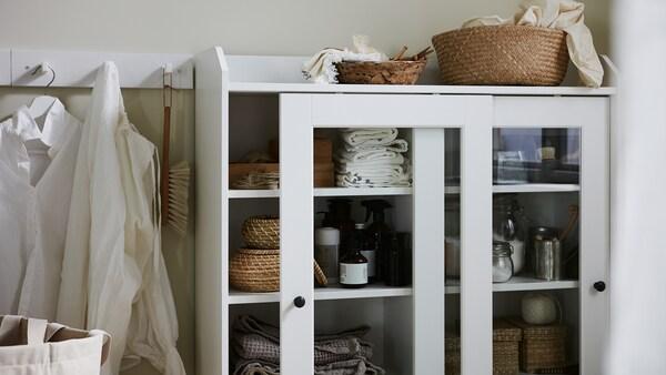 Ein Schrank mit Vitrinentüren, in dem Wäsche, Körbe und Waschutensilien zu sehen sind.