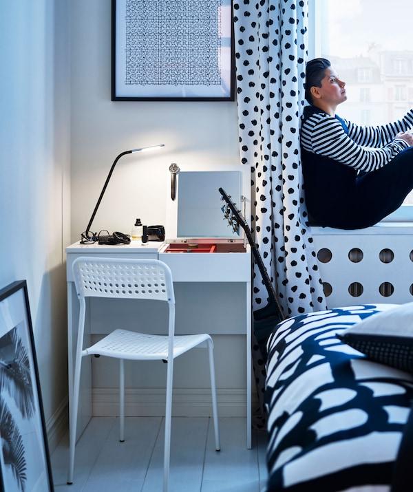 Ein schwarz-weiß gefleckter Schlafbereich, u. a. mit einem ADDE Stuhl in Weiß