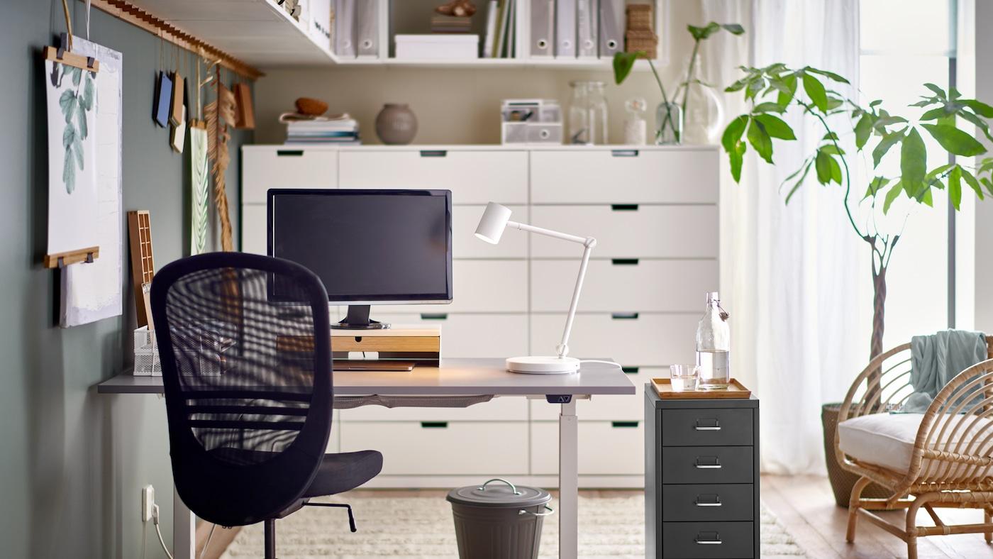 Ein schwarzer Drehstuhl und ein Schubladenelement neben einem Sitz-/Stehschreibtisch mit einer Arbeitsleuchte und einem Computerbildschirm.