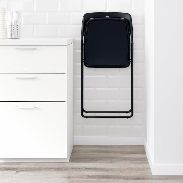 Ein schwarzer IKEA NISSE Klappstuhl hängt an einer weissen Wand an einer schmalen Stelle zwischen einer Wand und einem Schrank.