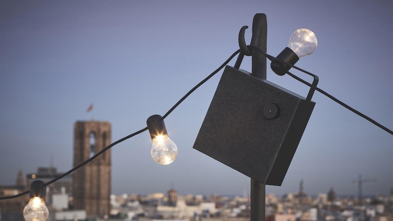 Ein schwarzer Lautsprecher mit Lichterkette im Freien.