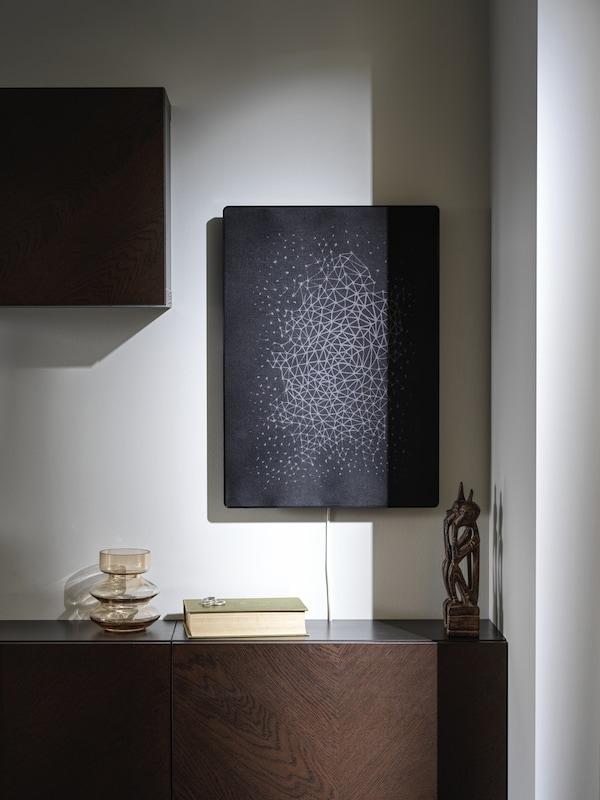 Ein schwarzer SYMFONSIK Rahmen mit WiFi-Speaker hängt an einer weißen Wand über einem Sideboard aus Holz.