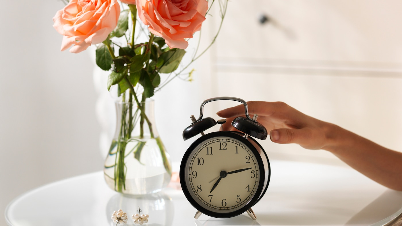 Ein schwarzer Wecker steht am Tisch, dahinter eine Vase mit orangenen Rosen