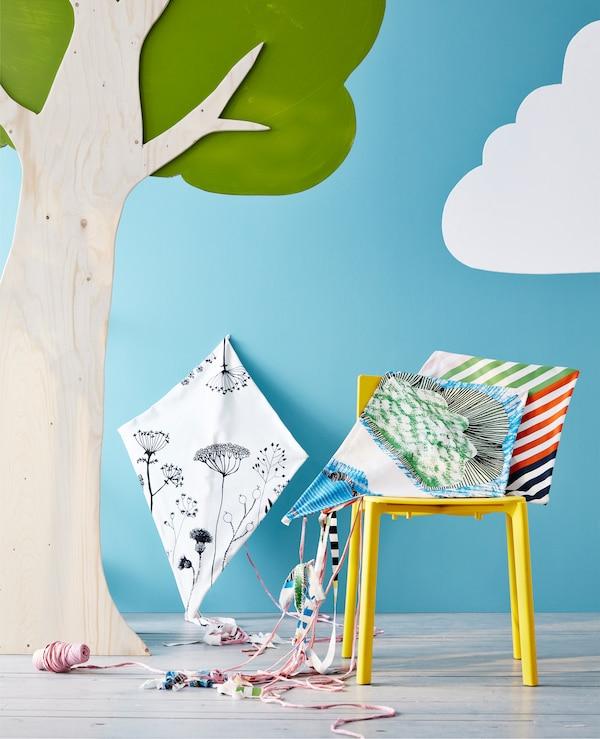 Ein selbst gebastelter Drachen auf einem Stuhl unter einem Baum