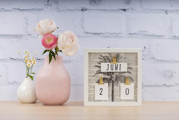 Ein selbstgebastelter Kalender steht neben einer Vase.