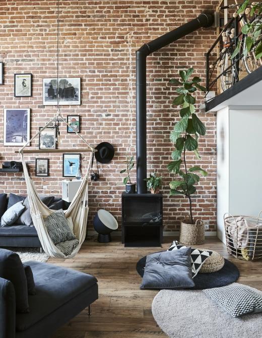 """Ein Sofa aus SÖDERHAMN Sitzelementen mit Bezug """"Samsta"""" in Dunkelgrau und eine Hängematte vor einer Wand aus Ziegelsteinen"""