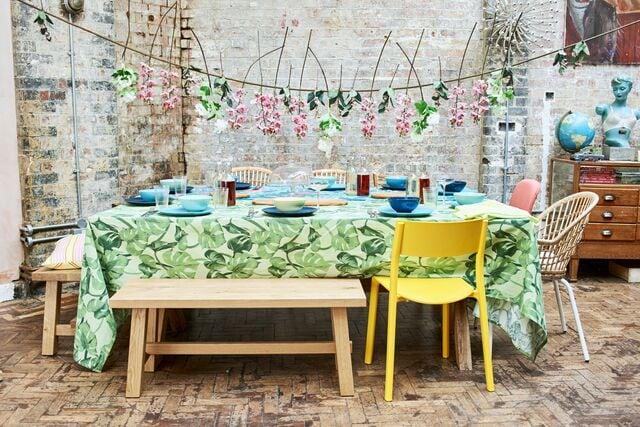 Ein sommerlicher Partytisch mit einer bunten Tischdecke, grünem und blauem Geschirr und einem NILSOVE/NORNA Stuhl mit Kissen in Weiß unter einer Kunstblumengirlande