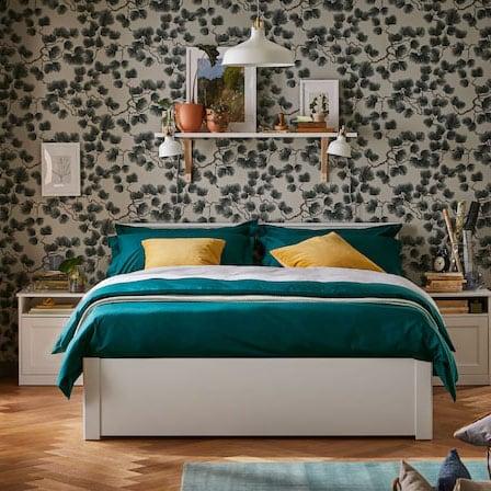 Ein SONGESAND Bettgestell in Weiss mit grüner Bettwäsche und gelben Kissen. Darüber befindet sich ein Regal an der Wand. Über dem Doppelbett hängt eine Hängeleuchte.