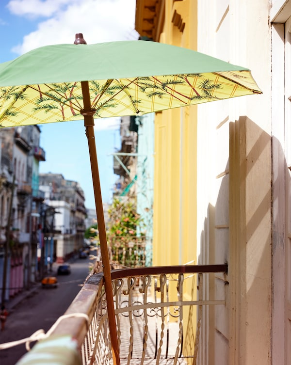 Ein Sonnenschirm mit einem aufgedruckten Muster in Grün und Gelb lehnt an das Geländer eines Balkons hoch über der Straße.