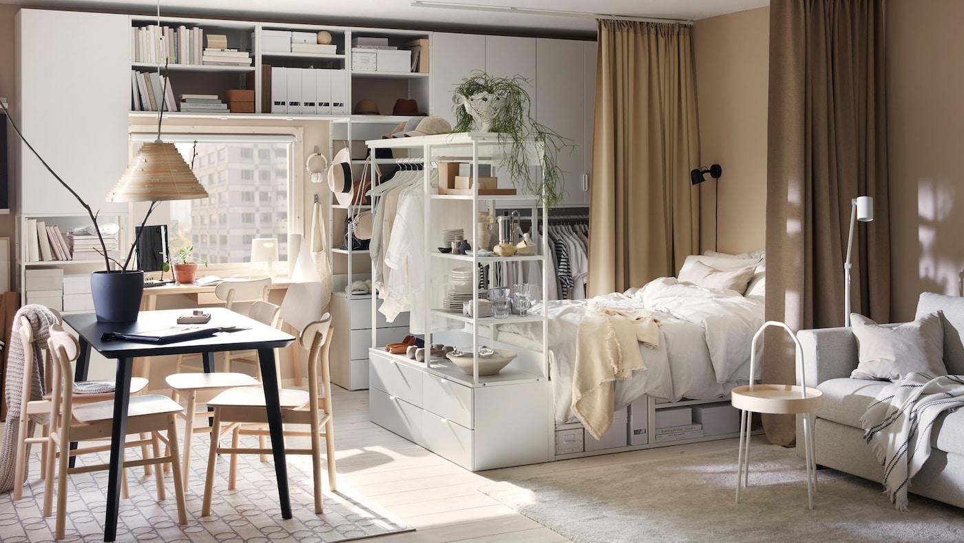 Ein sonniges Einzimmerappartment mit Aufbewahrungskombinationen, einem Bettgestell, einem schwarzen Tisch und Stühlen.