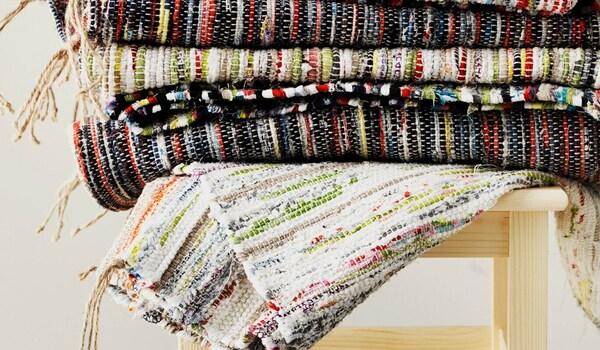 Ein Stapel handgemachter TÅNUM-Teppiche auf einem Hocker.