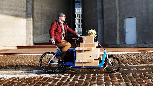 Ein Stapel IKEA Pakete auf einem Lieferfahrrad, das von einem Mann mit Brille gefahren wird.