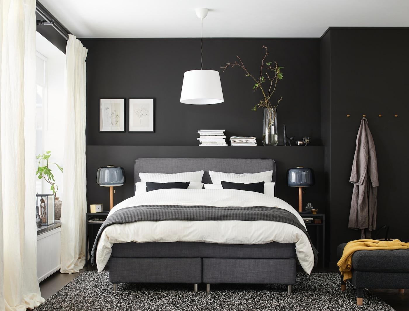 Ein stilvolles, dunkles Schlafzimmer mit einem Doppelbett, zwei Stehlampen und zwei dunklen Nachttischen.