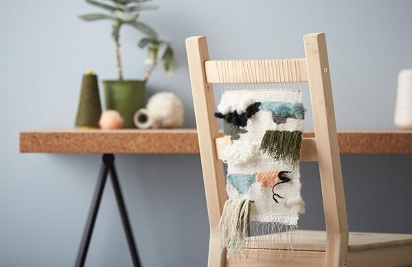 Ein Stuhl aus Holz mit einem weißen Stuhlbehang mit blauen, grünen und rosa Elementen steht vor einem Tisch.