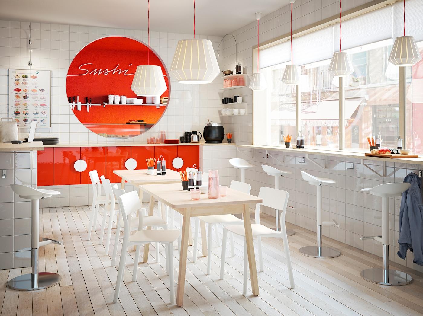Ein Sushi-Restaurant in Weiß & Orange mit vielen Sitzmöglichkeiten, Lampen & Küchenutensilien.