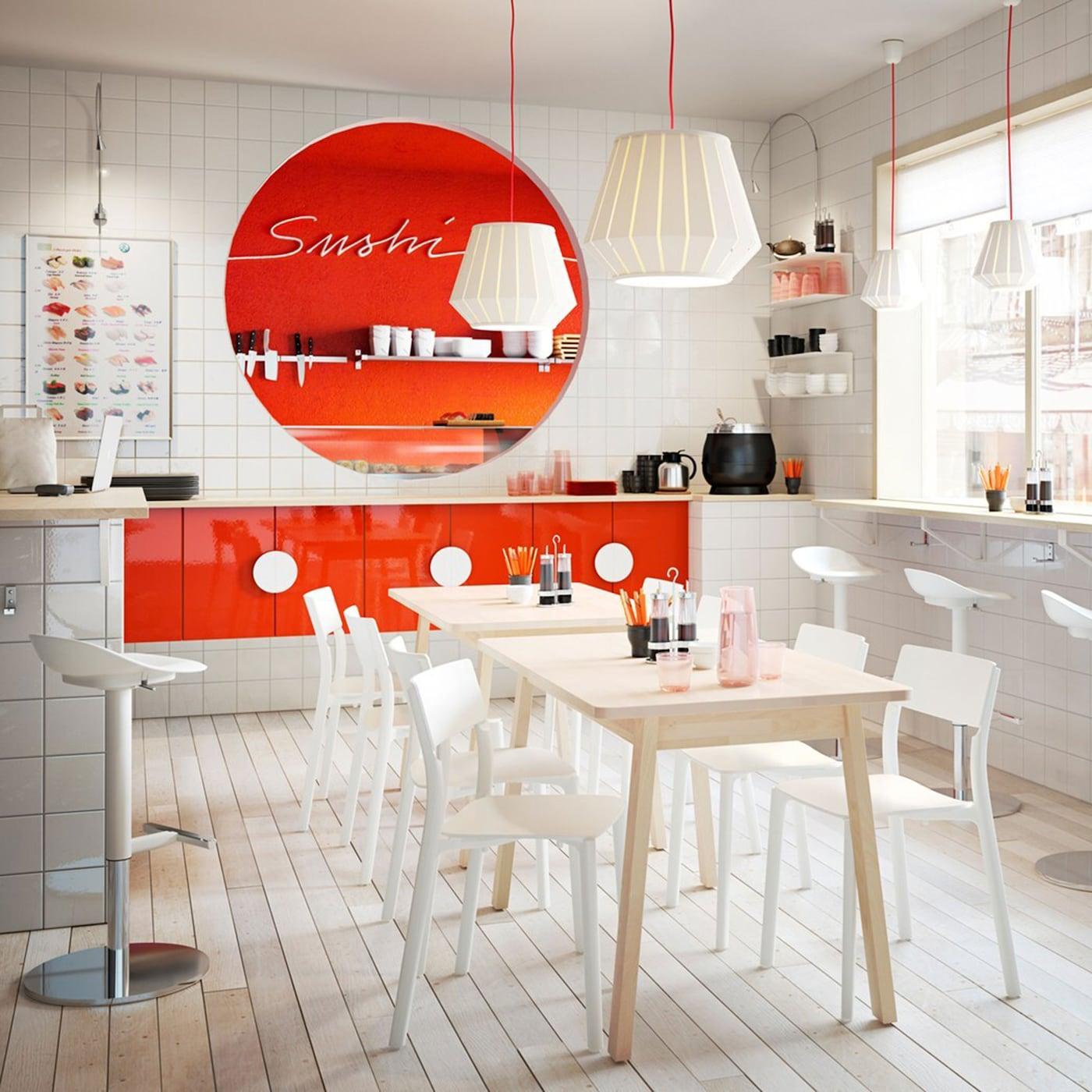 Ein Sushi-Restaurant in weiß und orange mit hohen und niedrigen Sitzmöglichkeiten.