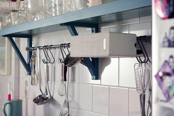Ein SYMFONISK Regal-WiFi-Speaker an einer gefliesten Küchenwand neben einer Stange voller hängender Küchenutensilien