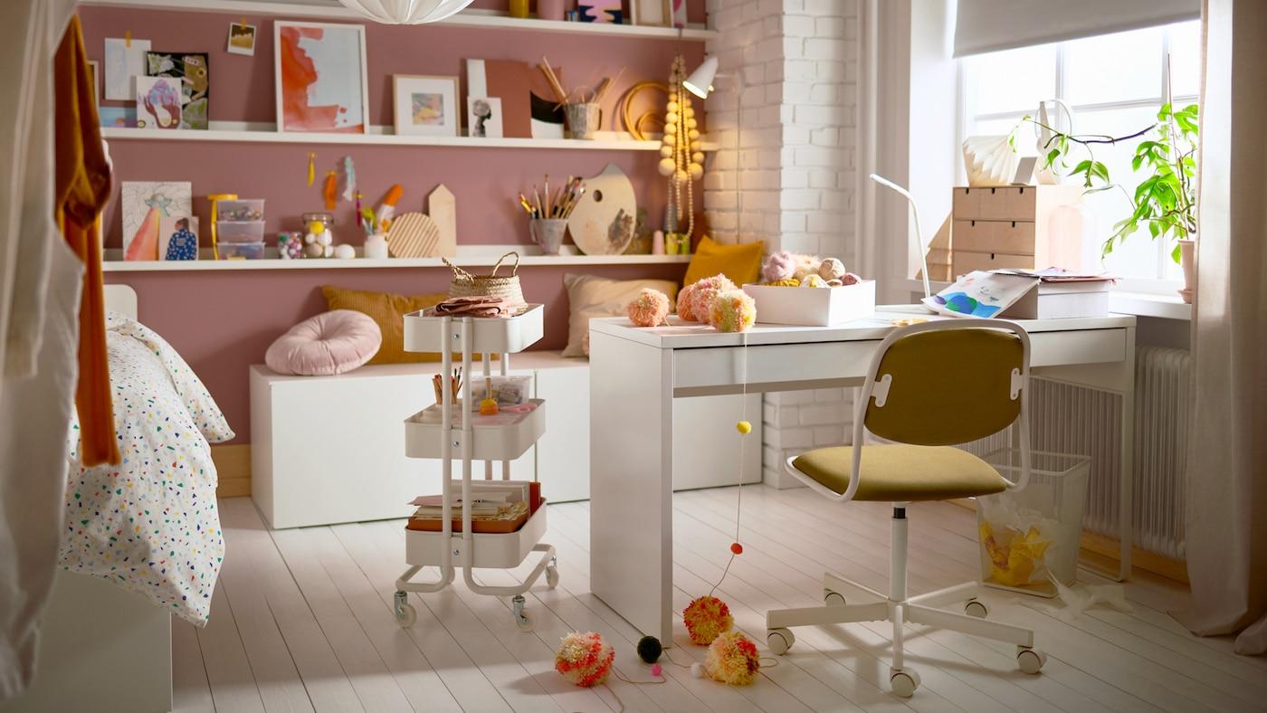 Ein Teenagerzimmer mit einem Schreibtisch, Rollwagen, Bilderleisten mit Deko, Kissen und einem Drehstuhl.