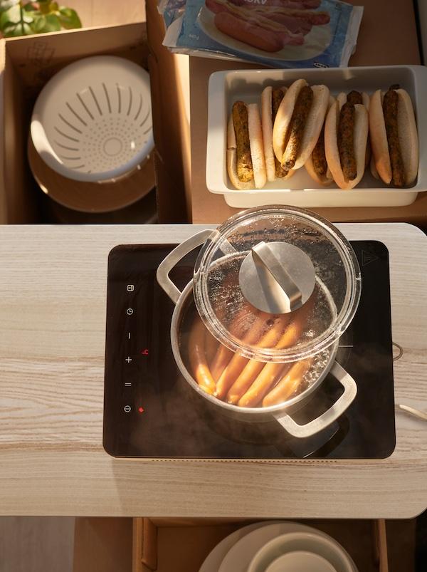 Ein TILLREDA Induktionskochfeld mit einem Topf mit Würstchen darauf. Daneben befinden sich Tabletts mit vegetarischen und fleischhaltigen Würstchen in Brot.