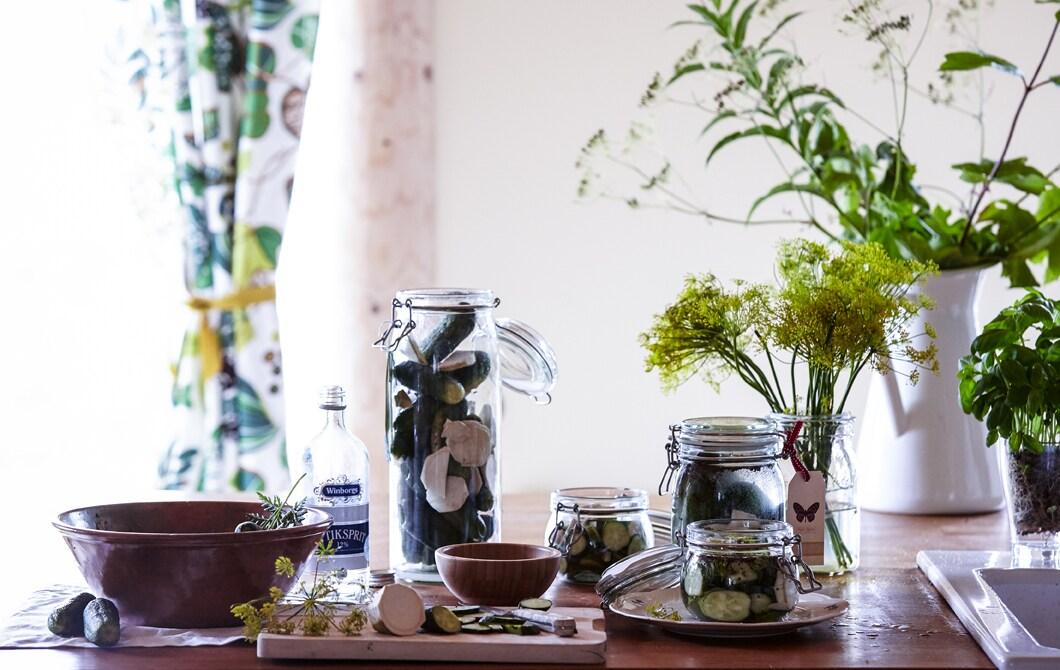 Ein Tisch auf dem verschiedene Schüsseln & Einmachgläser stehen mit eingemachten Gurken & Zucchini