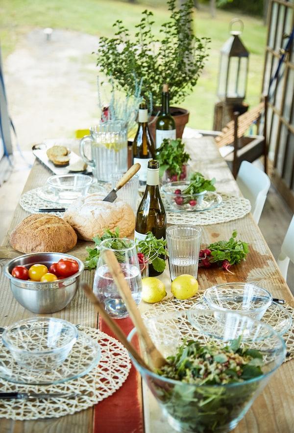 Ein Tisch mit Salaten und Pflanzen, u. a. mit TRYGG Servierschüssel aus Klarglas.