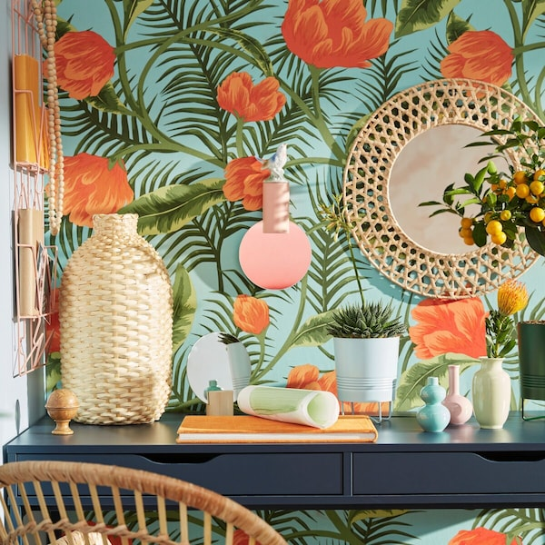 Ein Tisch mit Vasen und Spiegeln vor einer tropisch gemusterten Tapete.